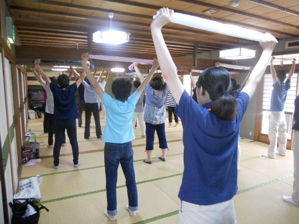 タオルを両手に健康体操を行う参加者の様子