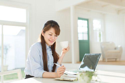 お茶を飲みながら仕事する女性