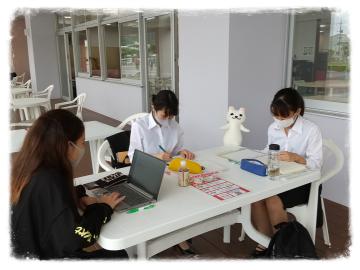 沖縄女子短期大学ウッドデッキで課題に取り組む学生たち