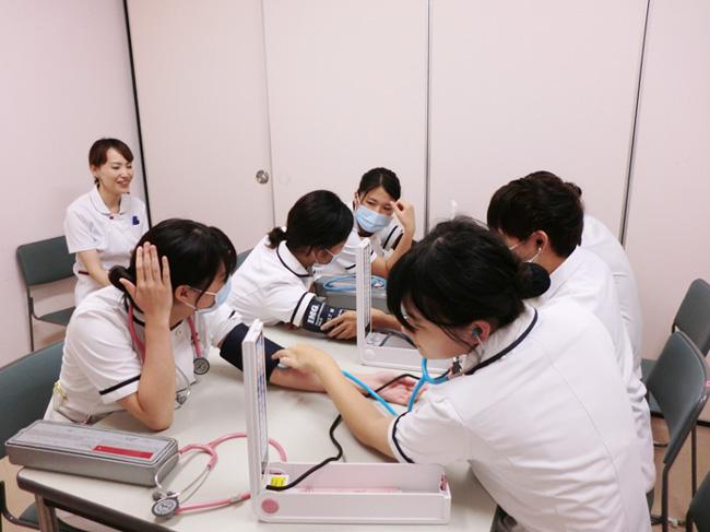 指導者から指導のもと、学生同士で血圧測定の練習をしている様子