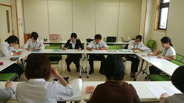 指導者の前で発表する学生